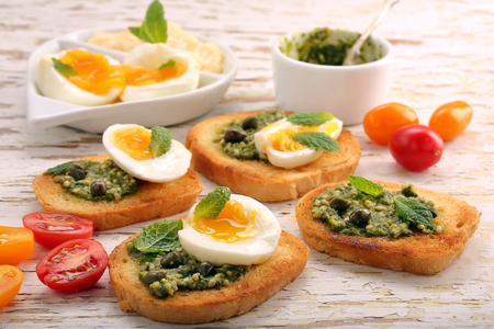 Fresh toast with pesto and eggs on wooden background