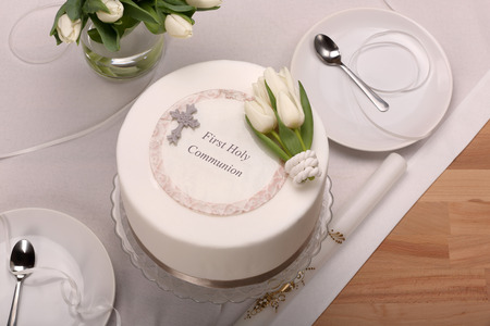 First holy communion cake on wooden background and empty space for text