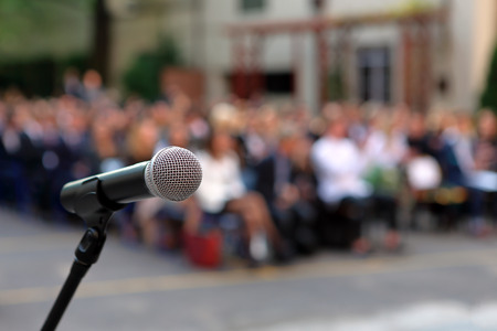 Microphone and stand in front of graduation ceremony audience against a background of auditorium and empty space for text Archivio Fotografico