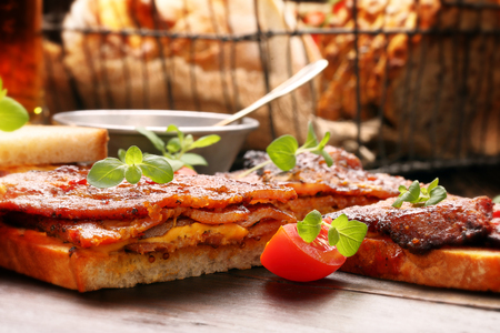 Beef sandwich with herbs and tomato on wooden board