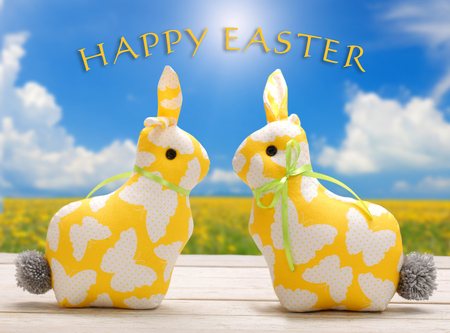 Two Easter yellow bunnies with happy easter text. Easter holiday concept.