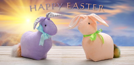 Two Easter bunnies with happy easter inscription. Easter holiday concept.