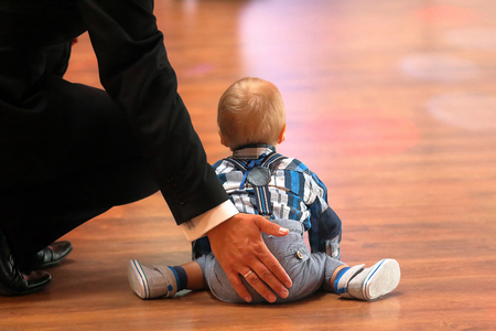 Little boy with dad learns to walk and empty space for text.