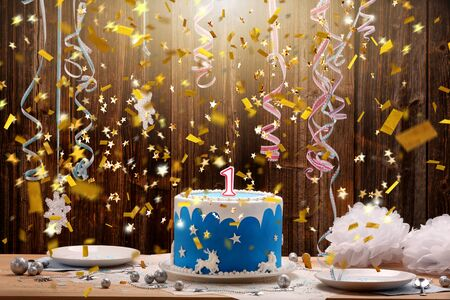 Birthday cake with one candle and confetti