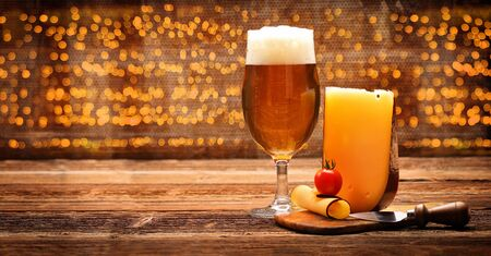 Yellow cheese appetizer with beer on wooden vintage background