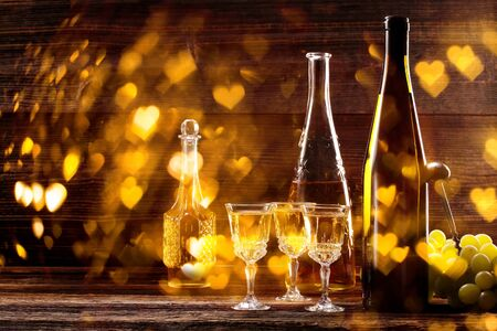 Wine bottle and glass on wooden vintage background and space for text
