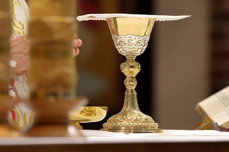 Chalice at the altar and Priest celebrate mass