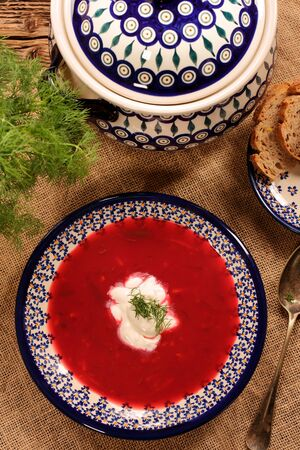 Ukrainian borscht with cream on wooden background