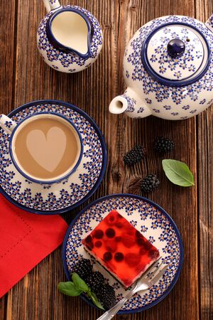 Sweet cake with fruit jelly and afternoon coffee on wooden background