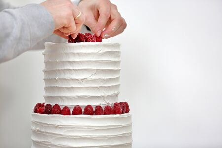 Confectioner decorates white wedding naked cake and empty space for text
