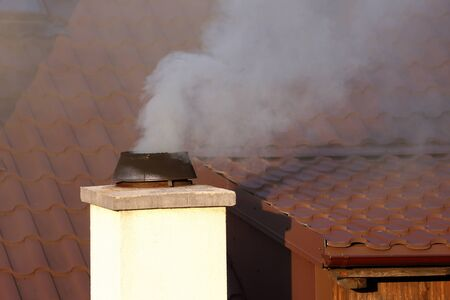Thick smoke coming out of the chimney causing air pollution  Stock Photo
