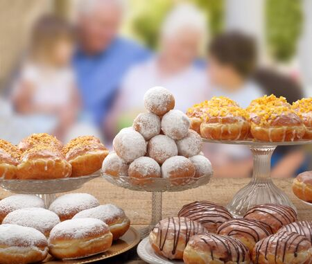 Fresh donuts on a plate and children with grandparents in the background and empty space for text