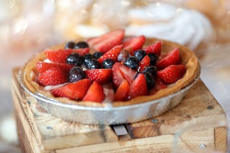 Vegetarian tart with strawberries and blueberries on a wooden background and empty space for text Stock Photo