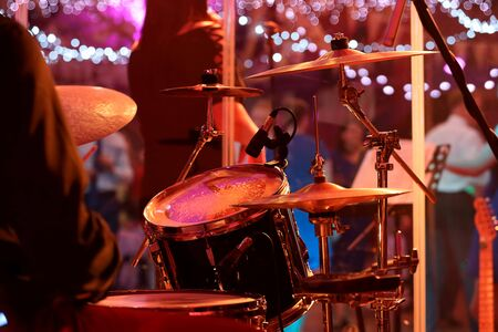 Drummer plays the drums during party event or wedding celebration and dancing couples in the background
