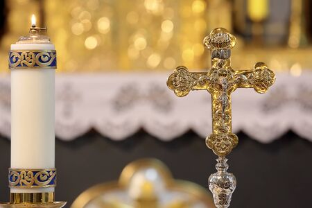 Holy cross with the crucified Christ and candle in the church with empty space for text