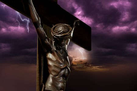Jesus Christ on the Cross sculpture against the stormy sky in background with empty space for text