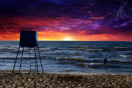 Beach during sunset and a woman entering the sea when the storm begins