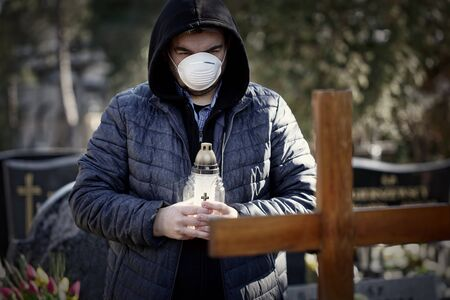 Man stands over the grave of a deceased coronavirus in the cemetery, wearing a protective mask.