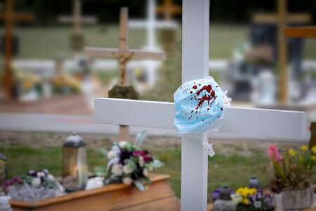 Cross on the grave of the deceased for coronavirus and a suspended anti epidemiological bloody protective mask