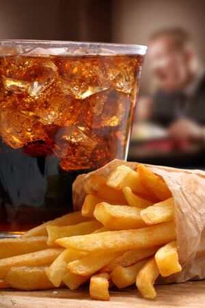 Fast food fries, cola with ice and a man eating in the background Zdjęcie Seryjne