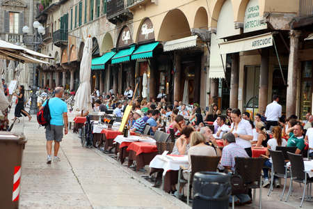Italy, Verona - 16 June 2019: Verona Erbe Square, crowd of tourists in a street restaurant Editorial