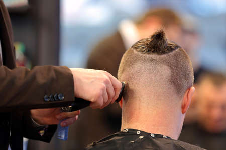 Barber cutting and modeling hair by electric trimmer at the hair salon Standard-Bild