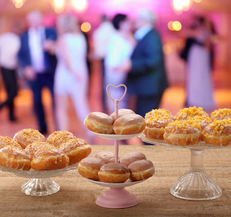 Fresh donuts on a plate and dancing people at the party in the background and empty space for text