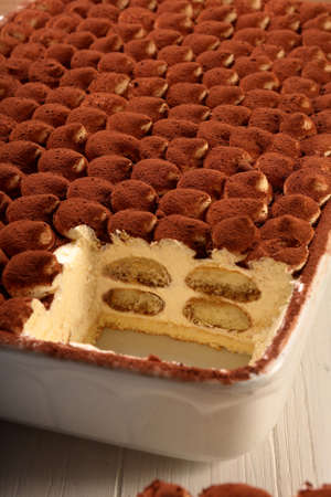 Classic tiramisu in a white dish and empty space for text