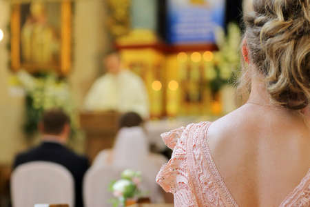 Woman sitting in a church during a wedding celebration against a priest and a young couple in the background and empty space for text Standard-Bild