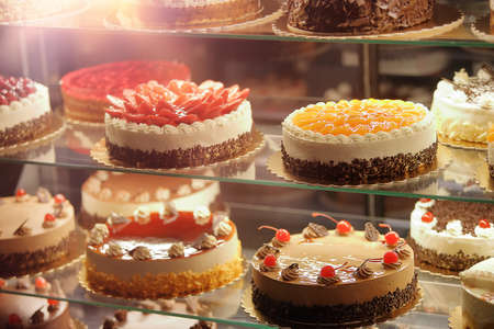 Various types of cakes in a pastry shop for sale and empty space for text