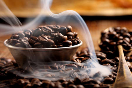 Roasted coffee and smoke on a brown background and empty space for text