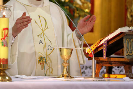 Chalice on the altar and priest celebrating mass in the background and empty space for text