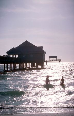 People wading in the water near pier at Clearwater Beach, Florida photo