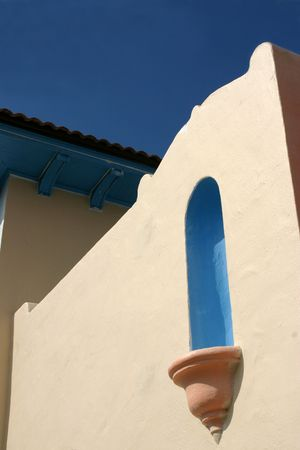 Detail of stucco wall against blue sky photo