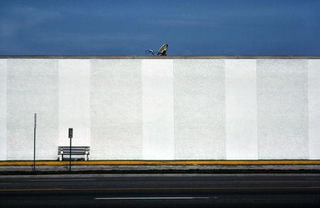 Satellietschotel en bank tegen getextureerde witte muur Stockfoto