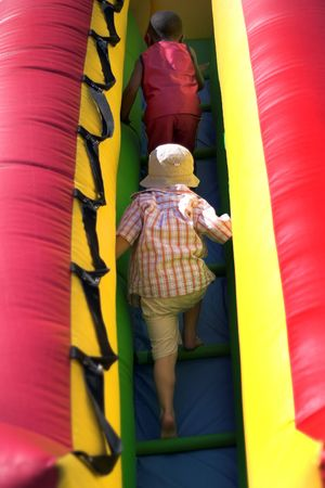 moonwalk: Young boys climbing inflatable bouncy at park playground Stock Photo