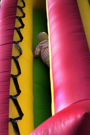 moonwalk: Young boy climbing through inflatable bouncy at park playground