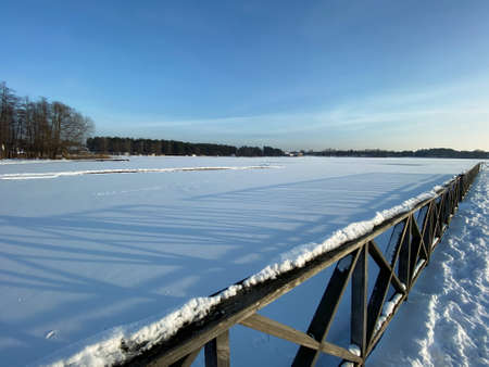View of the frozen Białe Lake near Włodawa with wooden decks a lot of snow just before sunset golden hour