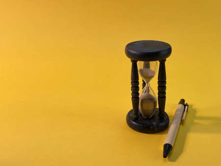 On a yellow background there is an hourglass measuring the time, next to it is a pen