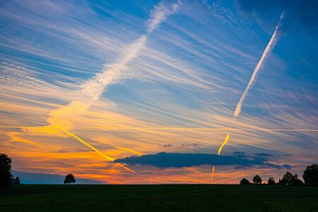 Condensation stripes on colorful evening sky