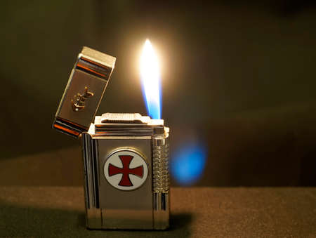Old used silver colored lighter with some scratches against a brown background. The flame burns. The lighter has a templar cross glued on and a fish