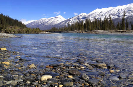 In the foreground wet pebbles and Kootenay River. The magnificent snow capped Canadian Rockies in the background. The serene beauty of the Rocky Mountains Standard-Bild
