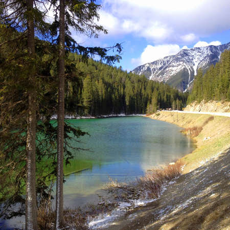 Olive lake in the Rocky Mountains. Kootenay National Park. Lovely green lake and forest. The highway and the magnificent snow capped Canadian Rockies on the right. A little bit of snow is still there. Standard-Bild