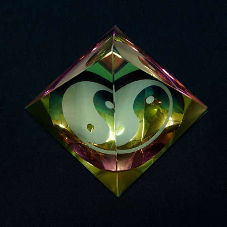 Pyramid glass object with a Yin and Yang sign in it. Black background Standard-Bild