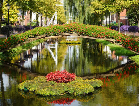 A town decorated with flowers. A kind of flower bridge has been built across the canal. A flower island with red begonias floats in the water. Reflections of the flowers in the water Standard-Bild