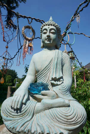 Statue of a sitting meditating buddha with a blue glass stone in his hand. Gautama. Blue sky