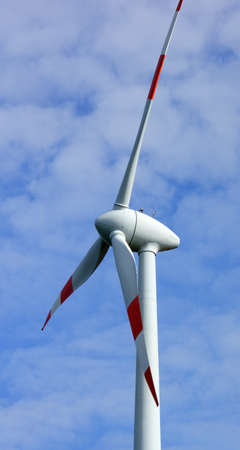 Close-up of a wind turbine creating alternative energy. Blue sky with clouds. Wind mill or wind turbine. Part of a wind farm. Sustainable energy concept. Green energy. Eco power.