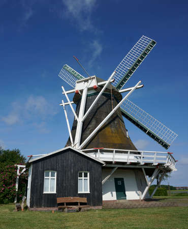A lovely smock mill in North Germany. In North Germany are a lot of historic windmills. It's a beautiful day with bright blue sky in summer.