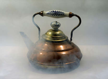 Old often repaired copper kettle. The blue white grip indicates a Dutch origin. There is steam around the kettle.
