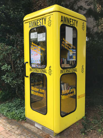 Papenburg, Germany - Sep 15 2019 Yellow phone booth of Amnesty International for book exchange Editorial